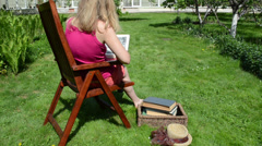 Woman in shorts read study thick book on wood chair Stock Footage