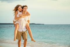 young couple in love walking on the beach at sunset - stock photo