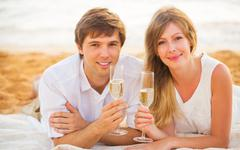 honeymoon concept, man and woman in love, enjoying glass of champagne on trop - stock photo