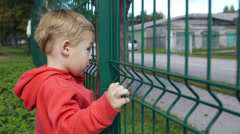 Little boy peering through a wire fence Stock Footage