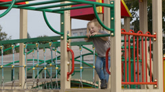 Boy on playground equipment. Stock Footage