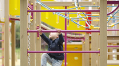 Cute little boy climbing on a jungle gym Stock Footage