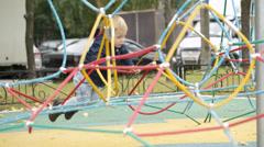 Happy little boy climbing on playground equipment Stock Footage