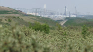 Stock Video Footage of View from dune crest Voorne Dunes at industrial area + pan tidal marshes