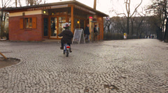 Kid and parent biking in Friedrischain Berlin in late fall Stock Footage