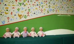row of sitting baby dolls in front of painted wall (abstract soccer stadium) - stock photo