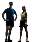 woman exercising fitness workout with man coach posing silhouette - stock photo