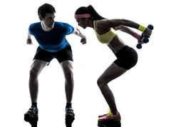 woman exercising fitness weight training with man coach silhouette - stock photo