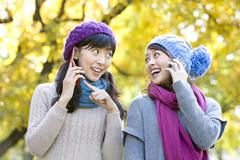 Two Young Woman on Mobile Phones, One Pointing - stock photo