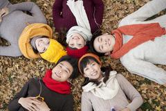 Friends Lying Amongst Maple Leaves Shaing MP3 Players Stock Photos