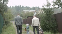 Two men and a boy walking in the countryside. Stock Footage