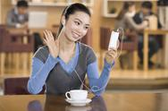 Excited young woman listening to music at a coffee shop Stock Photos