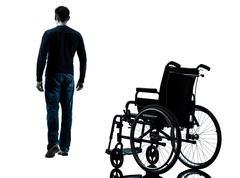 Man walking away from wheelchair silhouette Stock Photos
