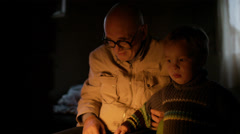 Grandfather and grandson near fire at home. Stock Footage
