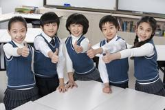 Five excited students in the classroom - stock photo