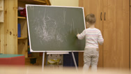 Stock Video Footage of Little boy drawing on a chalkboard at kindergarten