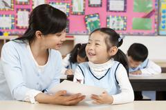 Teacher assisting student in class - stock photo
