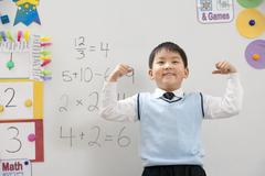 A young student flexing his muscles in front of a whiteboard - stock photo