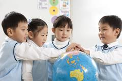 Four curious young students gathered around a globe Stock Photos