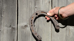Girl hand bracelet hang rusty horse shoe on wooden house wall Stock Footage