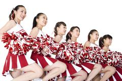 Cheerleaders performing a routine - stock photo