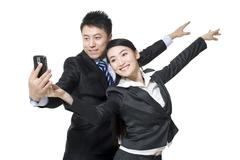A couple in business-wear dancing with a mobile phone Stock Photos