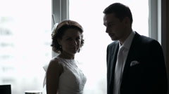 Bridal pair looking out the window. Stock Footage
