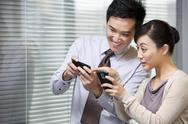 Stock Photo of Young Businessman and Businesswoman Comparing Pictures