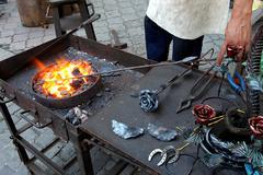 blacksmith wrought iron blacksmith anvil traditional metal jewelry - stock photo