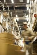 Blurred motion shot of Chinese warehouse worker pushing boxes - stock photo