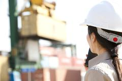 Shipping industry worker directing cranes with her walkie-talkie Stock Photos