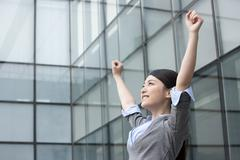 Stock Photo of Businesswoman with arms raised in celebration
