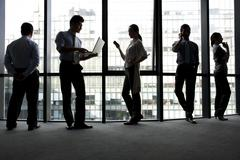 Silhoutte of businesspeople using technology Stock Photos