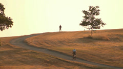 Mountain Cycling Through Field at Dusk 04 Stock Footage