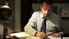 Young tired accountant working late with documents at his office HD Stock Footage