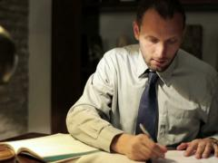 Young tired accountant working late with documents at his office NTSC Stock Footage