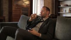 Young businessman drinking beer and watching TV on the sofa HD Stock Footage