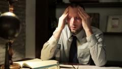 Overwhelmed businessman with headache working late at his office HD - stock footage