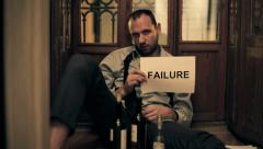 Drunk businessman showing failure sign, sitting on the floor HD Stock Footage