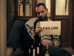 Drunk businessman showing failure sign, sitting on the floor NTSC Stock Footage