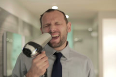 Young businessman singing to the blow-dryer in the bathroom NTSC Stock Footage