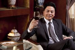 Mature businessman enjoying wine in a luxurious room - stock photo