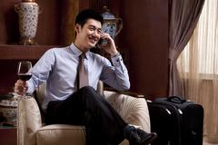 Young businessman using mobile phone in hotel - stock photo