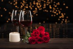 Romantic red wine, roses and white candle - stock photo