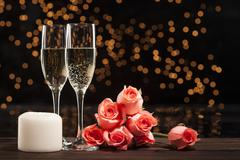 Romantic champagne, roses and white candle - stock photo