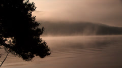 Morning mist moving over a mountain lake Stock Footage