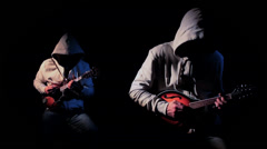 2 Mysterious Hooded Musicians Playing Mandolin in the Shadows - stock footage