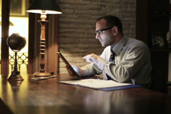 Accountant working on tablet late at night by the desk at home NTSC Stock Footage