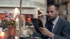 Businessman with modern tablet computer drinking coffee at the cafe HD Stock Footage