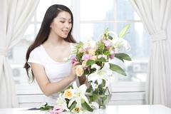 Young woman arranging flowers Stock Photos